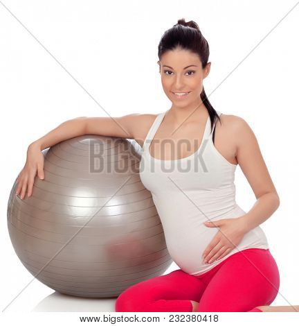 Brunette pregnant woman with a big ball doing exercices isolated on a white background