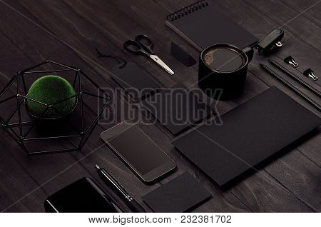 Modern Minimalistic Work Space With Black Blank Stationery, Coffee, Green Plant, Phone On Black Wood