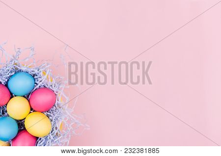 Easter Colorful Eggs In Fun Blue Nest On Soft Pink Background, Copy Space, Top View.