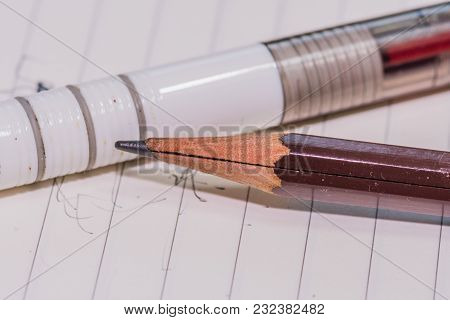 Closeup Of Broken Brown Wooden Pencil Laying In Front Of White Plastic Pen On Lined White Paper With