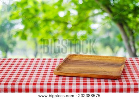 Empty Wooden Tray On Table Over Blur Trees With Bokeh Background, For Food And Product Display Monta