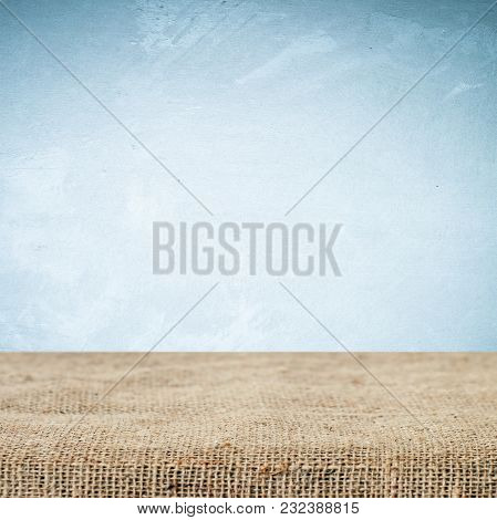 Empty Table And Sack Tablecloth Over Grunge Cement Wall Background, Product Display Montage, Vintage