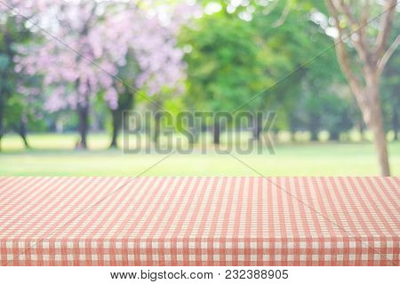 Empty Table With Pink And Beige Scott Pattern Tablecloth Over Blur Park Background, Food And Product