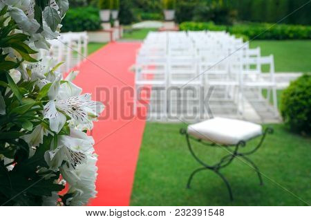 Rustic altar decorated with lilies, alstroemerias and chrysanths behind de red carpet with whites ch