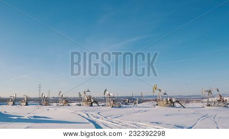Working Oil Pumps In The Winter Field On The Background Of The City, Petroleum Industry