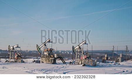 Working Oil Pumps In The Winter Field, Petroleum Industry