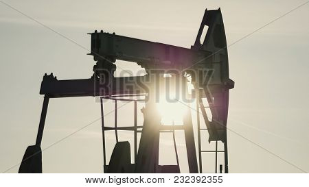 Close-up Of Working Oil Pump In The Background Of The Sun, Petroleum Industry