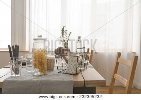 Interior View Of Wooden Simple Table With Products And Utensils In Daylight.