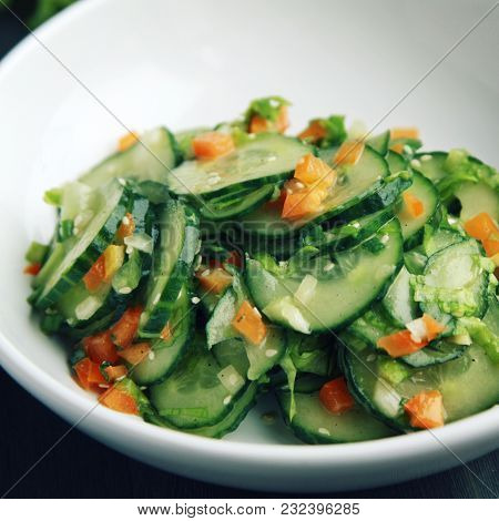 Chinese Cucumber Salad On The White Plate. Asian Cuisine. Bell Pepper, Cucumber And Sesame Seeds. Ve