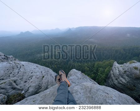 Legs Of A Man On Rock. Hiker Resting In Boots For Mountain Tracking Against The Backdrop Of Valley W