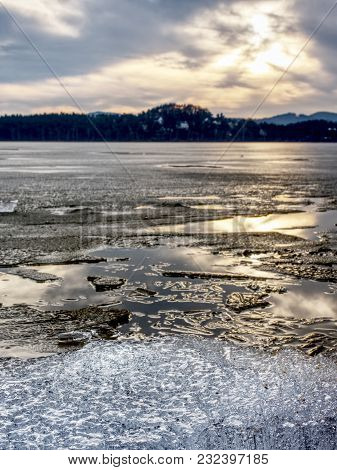 Exposed Shore Under Melting Ice. Close Up View To Border Between Ice And Dark Water.  Warm Summer On