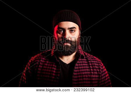 Bearded Hipster In Studio Portrait With Two Colored Red Lights From Behind