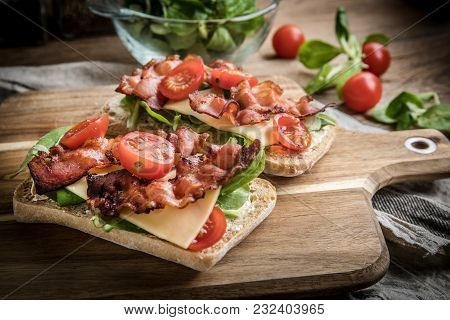 Ciabatta Sandwich With Arugula Salad, Bacon And Yellow Cheese.
