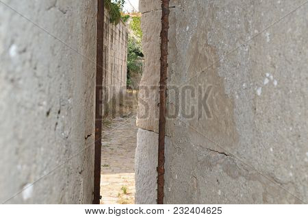 Paved Alley In An Abandoned Fortress Seen While Peeking Through Two Walls