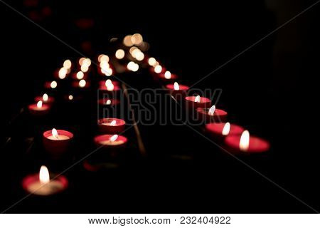 Many Red Candles Lit, With Bokeh, In A Very Dark Ambient