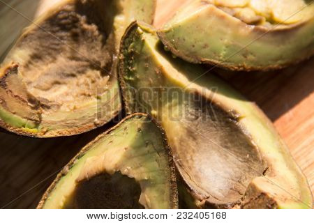 Four Pieces Of Rotten Avocado On Wooden Background