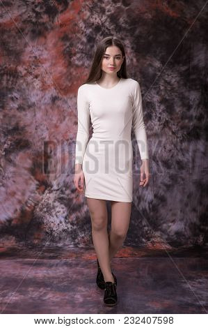 Picture Of Young Brunette Woman In White Dress On Marble Multicolored Background. Model Test.