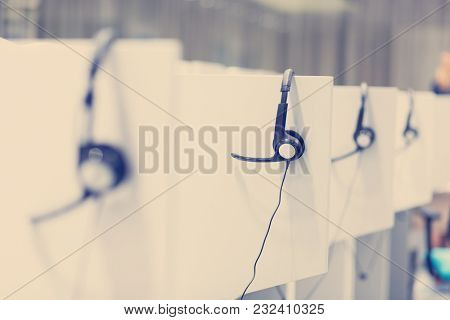 Headphones hanging on cubicle partition in empty call center office