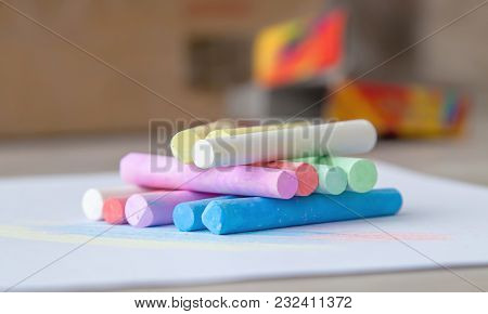 Color Chalk In The Form Of Sticks With A Colored Back. Behind The Crayons Are Seen Color Spots With