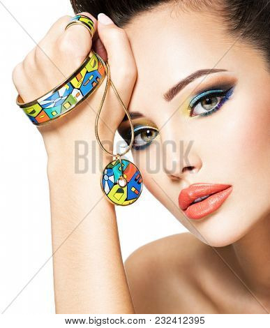 Beautiful woman with creative bright colored make-up. Fashion girl with glamour jewelry