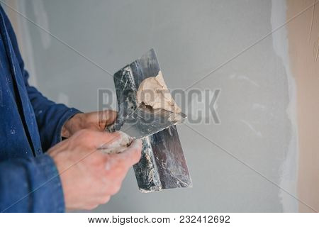 Hands Of The Plasterer Worker Tool Putty Trowels