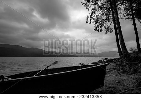 Small Fishing Boat Silhouette At The Shore With Partial Pines In Cloudy Dark Rainy Morning At Lake D