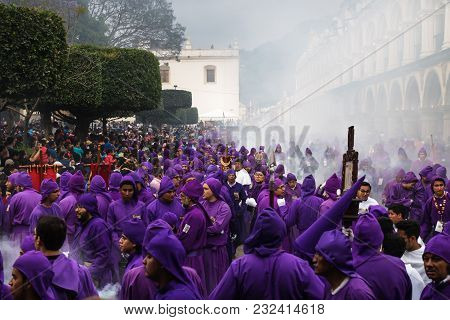 Antigua, Guatemala: March 18 2018: Purple Robed Men In Thick Incense Smoke At The Procession San Bar