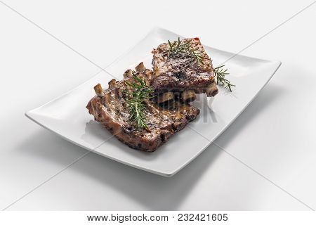 White Rectangular Plate With Baked Pork Ribs Isolated On White Background