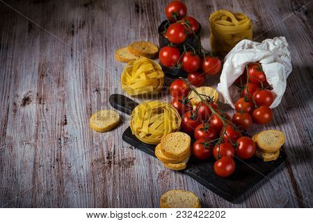 Red Cherry Tomatoes On Wooden Table With Tagliatelle And Bruschetta