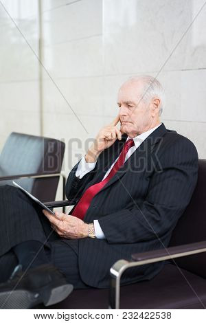 Portrait Of Concentrated Senior Caucasian Businessman Wearing Formal Suit Using Touchpad Searching F