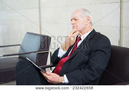 Portrait Of Pensive Senior Caucasian Businessman Wearing Formal Suit Using Digital Tablet, Following