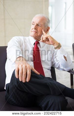 Portrait Of Concentrated Senior Caucasian Leader Wearing Shirt And Tie Sitting In Armchair In Office