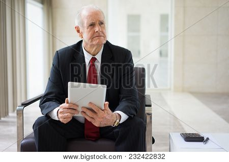Portrait Of Confident Senior Caucasian Financial Adviser Sitting In Armchair With Touchpad And Calcu