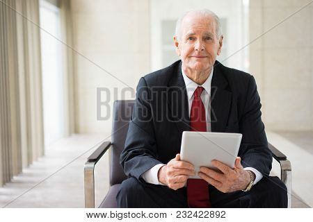 Portrait Of Confident Senior Caucasian Manager Sitting In Armchair With Digital Tablet And Looking A