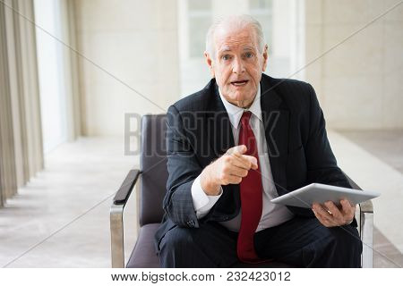 Portrait Of Experienced Senior Caucasian Mentor Sitting In Armchair With Digital Tablet And Giving B