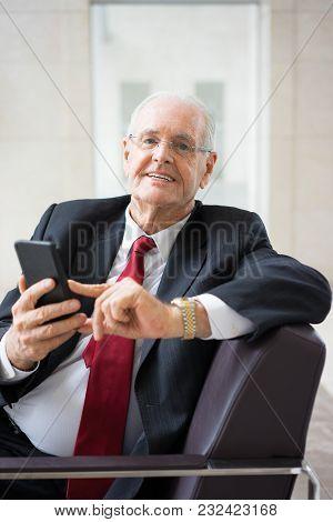 Portrait Of Happy Senior Caucasian Executive Using Mobile Phone And Smiling At Camera. Senior Leader