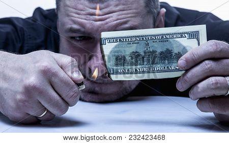 Money Is Not The Best Method Of Employee Motivation. Close Up A Man Burns A Hundred Dollar Bill.