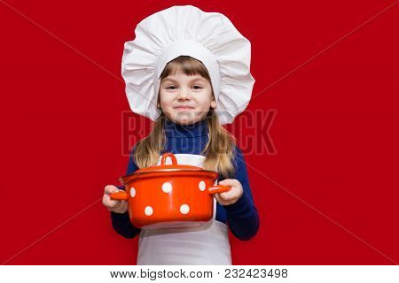 Happy Little Girl In Chef Uniform Holds Saucepan Isolated On Red. Kid Chef. Cooking Process Concept