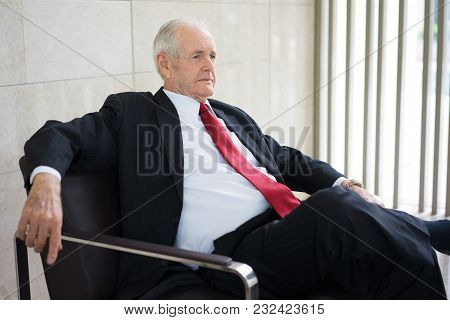 Portrait Of Serious Senior Caucasian Ceo Wearing Formal Suit Sitting In Armchair At Meeting. Senior