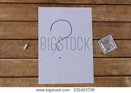The Pill And A Condom . On The Background Of Wooden Table .