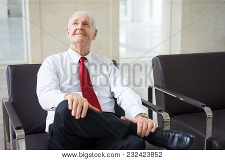 Portrait Of Caucasian Senior Employee Wearing Shirt And Tie Sitting In Armchair In Boardroom And Smi