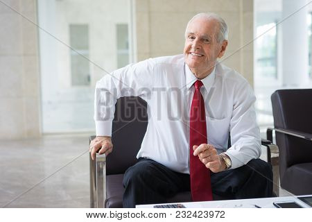 Portrait Of Successful Senior Caucasian Executive Wearing Shirt And Tie Sitting In Armchair In Moder