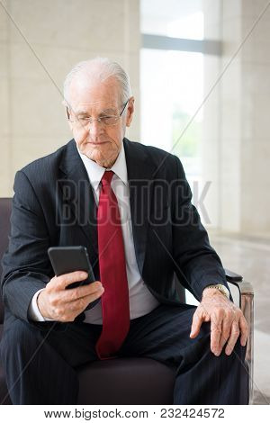 Portrait Of Senior Caucasian Businessman Wearing Glasses Sitting In Armchair And Texting Or Reading