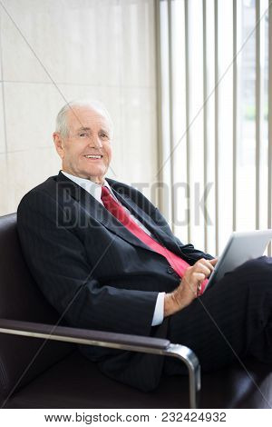 Portrait Of Successful Senior Caucasian Businessman Wearing Formal Suit Sitting In Armchair With Lap