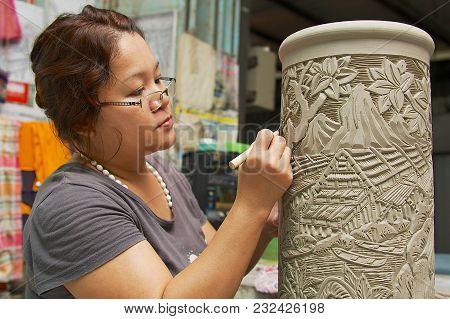 Kuching, Malaysia - August 27, 2009: Unidentified Woman Cuts Traditional Tribal Tattoo Motives Decor