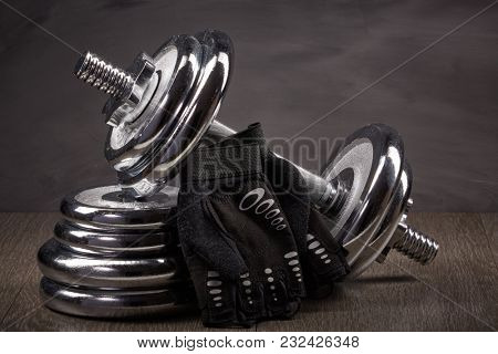 Steel dumbbell and weights on grey background. Sports bodybuilding equipment. Fitness, sport or healthy lifestyle concept.
