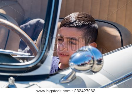 Beit Nir, Israel - March 17, 2018: Little Boy Sit In Triumph Car, Presented On Oldtimer Car Show, Is