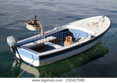 Little Wooden Boat With Outboard Engine Anchored In Calm Port