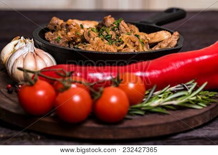 Close Up Frying Pan With Roasted Pork And Garlic, Pepper, Rosemary And Tomatoes On Dark Wooden Backg