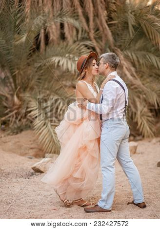 Bride In Hat And Groom Stand On Sand, Embrace And Kiss Against Backdrop Of Palm Trees.